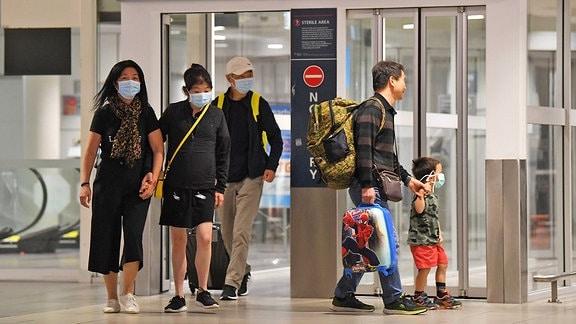 Passagiere mit Mundschutz auf dem Flughafen von Sydney