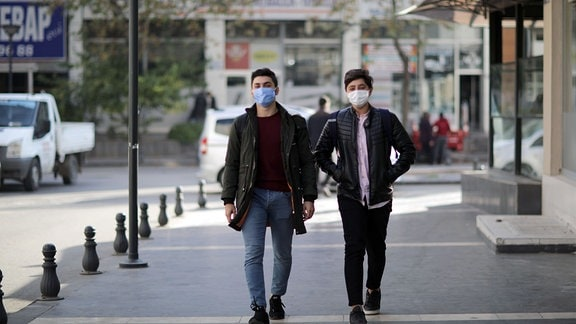 Zwei männliche Jugendliche mit Schutzmasken laufen auf einer Straße im südtürkischen Gaziantep, Frontalblick, Hintergrund leicht unscharf