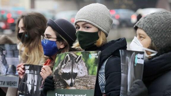 Junge Anti-Pelz-Aktivist/-innen mit Masken stehen perspektivisch schräg aufgereiht,  halten während der Demonstration Plakatee mit Text in kyrillischen Buchstaben und Fotos verschiedener Pelztiere hoch.