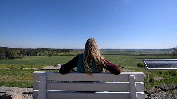 Eine Frau sitzt auf einer Bank unter blauem Himmel