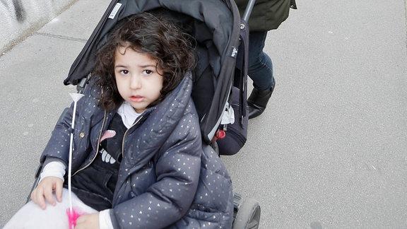 Passantin mit Mundschutz schiebt Kind im Kinderwagen
