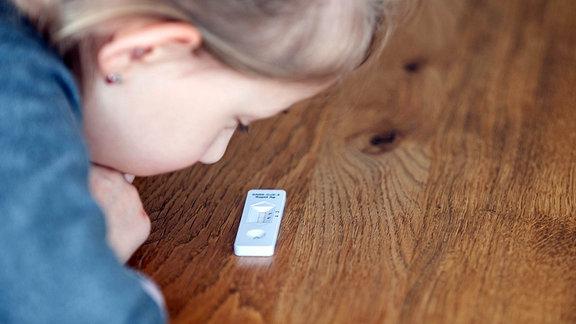Ein kleines Mädchen schaut auf einen Corona Antigen Test