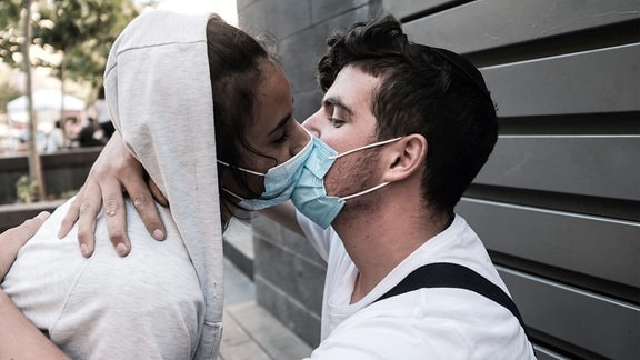 Ein junges Paar experimentiert damit, seine Zuneigung in der Öffentlichkeit mit obligatorischen Gesichtsmasken auszudrücken.