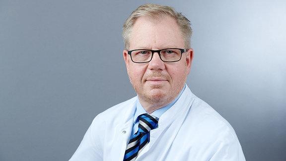 Mann mit Brille im weißen Kittel