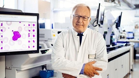 Mann mit Brille in einem Labor neben einem Bildschirm