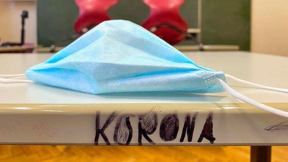 Mundschutzmaske und Schriftzug KORONA auf einem Tisch in einem leeren Klassenzimmer, im Hintergrund unscharf hochgestellte Stühle und Tafel
