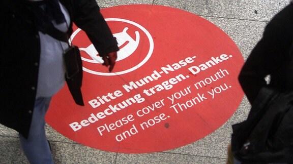 GroÃßer Aufkleber mit Piktogramm und Aufschrift Bitte Mund und Nase bedecken klebt auf dem Boden im Hauptbahnhof München