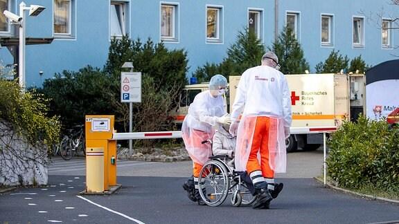 Zwei Pflegekräfte der Johanniter bringen eine Heimbewohnerin auf einem Rollstuhl aus einem Seniorenheim