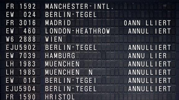 Schwarze Abflugtafel am Flughafen Köln/Bonn mit weißen Text: Verschiedene Flugnummern und Flugziele, einige davon als annuliert.