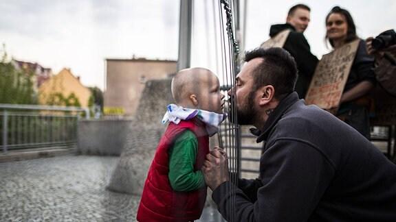 Ein kleines Kind trifft auf sein Vater auf der gegenueberliegenden Seite der Grenze Zgorzelec und Goerlitz an einem Metallzaun, Seitenansicht, Kussposition