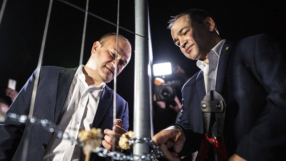 Octavian Ursu Oberbürgermeister der Stadt Goerlitz und Rafal Gronicz, Bürgermeister der Stadt Zgorzelec – zwei Männer löse das Schloss an einer Metallkette an einem Zaun. Froschperspektive im Dunkeln mit beleuchteten Gesichtern.