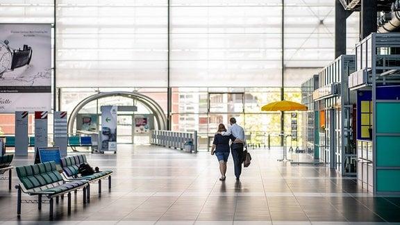 Impressionen vom Geschehen auf dem Flughafen Dresden International nach dem Neustart des Flugbetriebs: Blick in die leere Abflughalle. Ein Paar läuft Arm in Arm Richtung Ausgang, Blick von hinten.