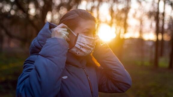 Eine junge Frau legt eine selbstgemachte Schutzmaske an