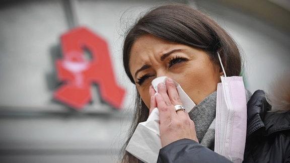 Junge Frau, mit am Ohr hängendem Mundschutz, putzt sich die Nase