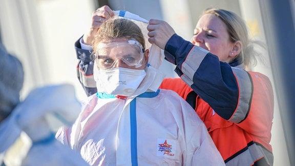 Eine Sanitäterin hilft einer weiteren Person beim Anziehen eines Schutzanzuges.