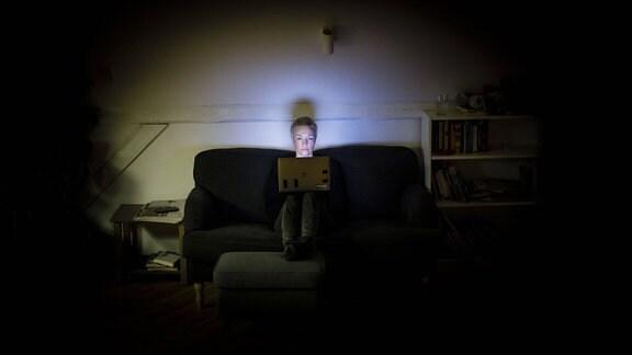 Eine Frau sitzt nachts auf der Couch und schaut in ihren Laptop.