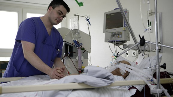 Pfleger betreut einen künstlich beatmeten Patienten auf der Intensivstation.