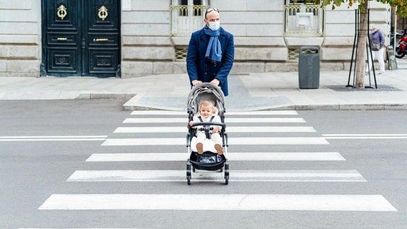 Ein Mann mit Mund-Nasen-Schutz schiebt einen Kinderwagen.