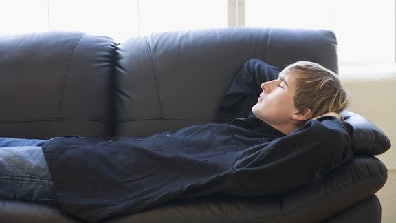 Ein Mann liegt auf einem Sofa.