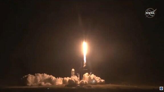 Eine Rakete startet in den Nachthimmel