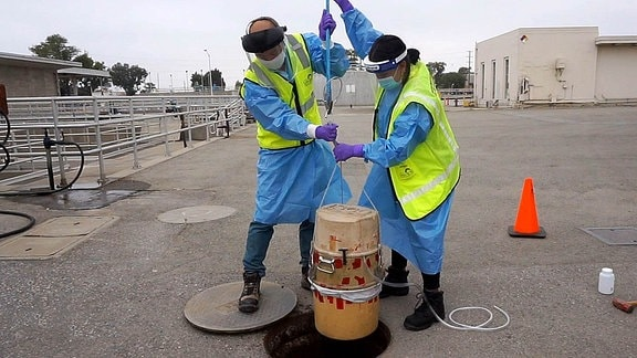 Die Umweltinspektoren des Umweltdienstes der Stadt San José, Isaac Tam und Laila Mufty, setzen einen Autosampler in einen Schacht der regionalen Abwasseranlage San José - Santa Clara ein.