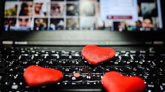 Rote Herzen liegt auf der Tastatur eines Notebooks, im Hintergrund ist die Webseite einer Internet-Partnerbörse zu sehen.