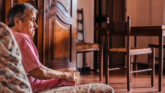 Seitenansicht in warmen Licht: Ältere Frau sind auf einem Sofa in einem Wohnzimmer und schaut leicht nach unten. Im Hintergrund Wohnzimmerschrank,, Tisch und Stühle aus Holz.