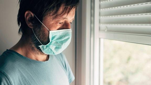Ein Mann mit Munschutz schaut aus einem Fenster