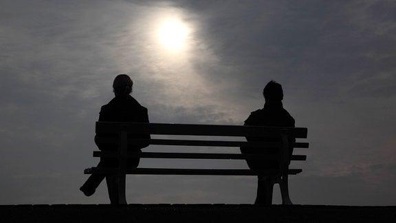 Silhouette von einem Mann und einer Frau, auf einer Bank sitzend.