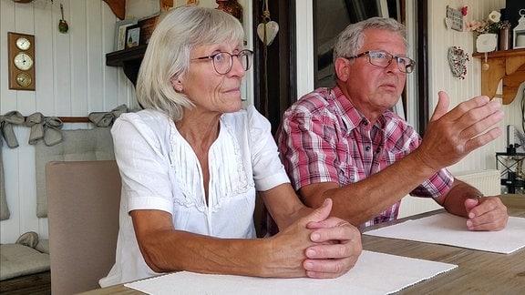 Älteres Paar sitzt erzählend am Tisch.