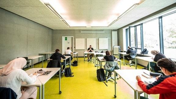 Ein Lehrer unterrichtet Deutsch in einer Klasse, die wegen Corona geteilt wurde