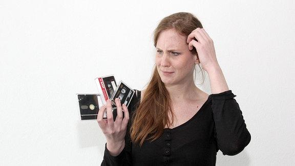 Eine Frau schaut fragend auf zwei Kassetten und eine Diskette, die sie in ihrer rechten Hand hält.