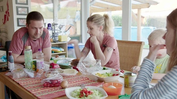 Eine Familie sitzt am Tisch.