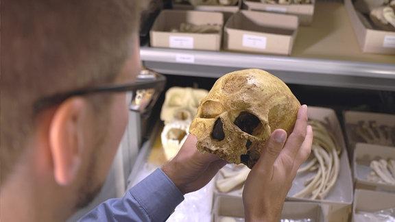 Ein junger Mann hat einen Schädel in Händen