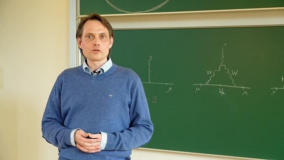 Ein Mann im blauen Pullover vor eienr grünen Tafel, auf der Formeln aufgeschrieben sind