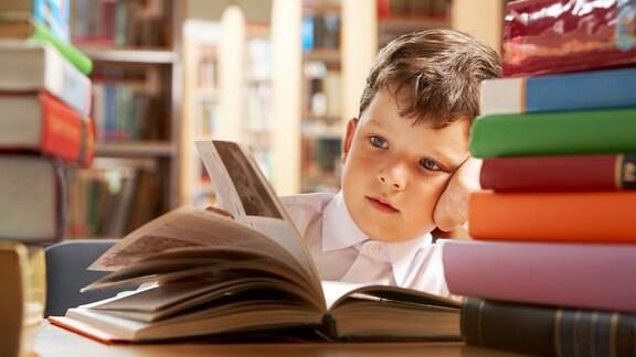 Junge sitzt lesend in einer Bibliothek