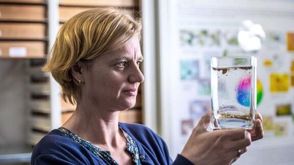 Dr. Doreen Werner hält ein Glasbehälter mit Mückenlarven im Wasser in den Händen.