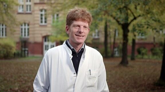Mann  im weißen Medizinkittel steht in einem Park unter Bäumen