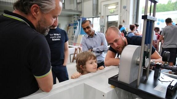 Ein Ingenieur führt Besuchern ein Experiment an einem Betonkanal vor.