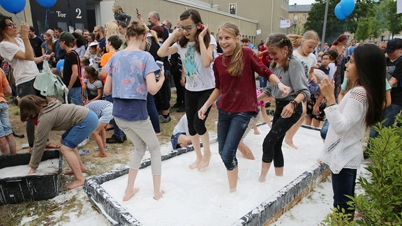 Jugendliche Mädchen stacksen mit nackten Füßen durch ein Becken, in dem sich eine hellgraue Flüssigkeit befindet.