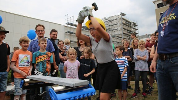 Eine junge Frau mit Handschuhen und einem Schutzhelm schwingt einen großen Hammer über ihrem Kopf. Vor ihr liegt ein Betonblock.