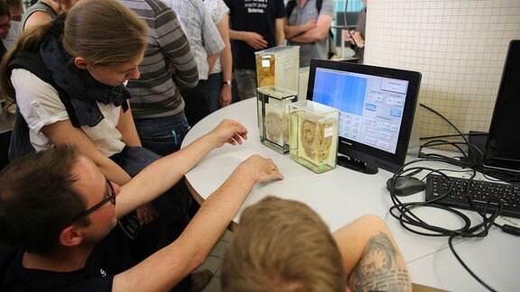 Besucher stehen vor drei medizinischen Präparaten, die auf einem Schreibtisch mit einem Computer aufgebaut sind.