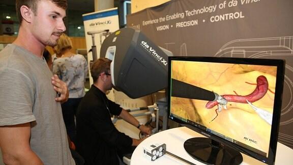 Ein Mann steht vor einem Computerbildschirm, der eine Großaufnahme davon zeigt, wie ein Chirurgieroboter eine winzige Operation durchführt.
