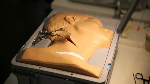 Gummiabgus von einem menschlichen Kopf und dem Hals. Dort hält eine Zange einen Luftröhrenschnitt offen.