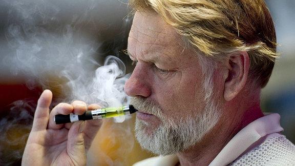 Ein Mann zieht an einer E-Zigarette.