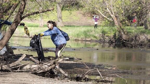 Jugendliche sammeln Müll an einem Fluß ein.