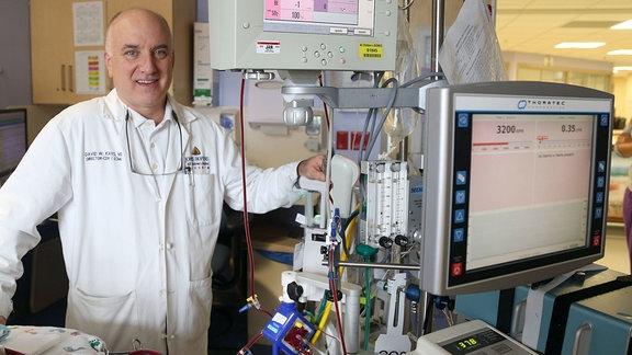 Ein Arzt steht neben einer Herz-Lungen-Maschine und schaut lächelnd in die Kamera.