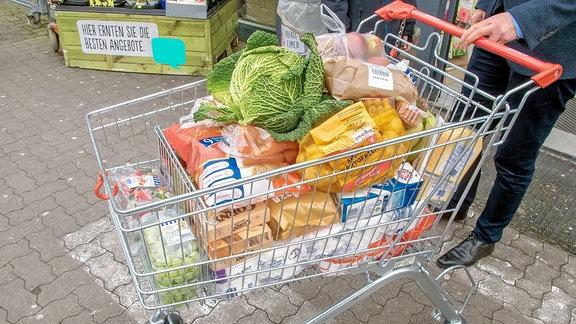 Gut gefüllter Einkaufswagen vorm Supermarkt.