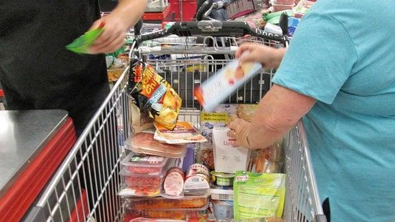Voller Einkaufswagen an einer Supermarktkasse