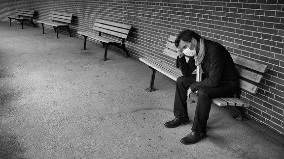 Mann mit Mundschutzmaske sitzt nachdenklich auf einer Bank